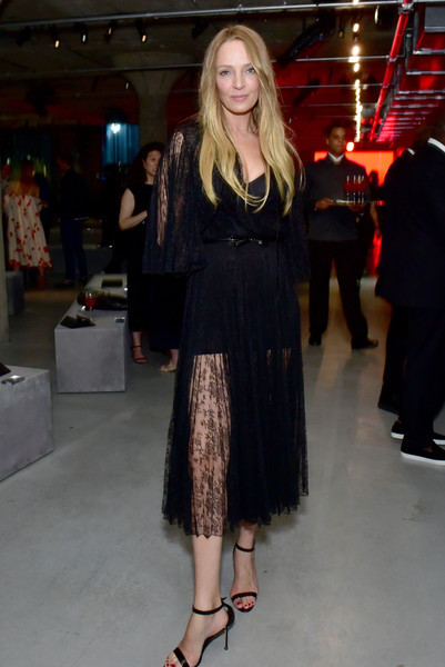 Uma Thurman looked sultry and elegant in a sheer black lace dress by Prada during the brand's Resort 2019 show.