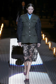 Gigi Hadid looked tough up top in a two-tone military jacket while walking the Prada runway.