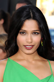 Freida Pinto paired her bright green dress with a dark berry pout. She finished off the look with colorful jewelry and tousled waves.