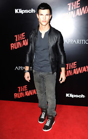 Taylor took his looke from day to night when he topped off his casual look with a zip-up leather jacket.