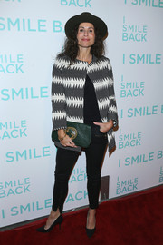Minnie Driver accessorized with a green Gucci clutch for a splash of color to her monochrome outfit.