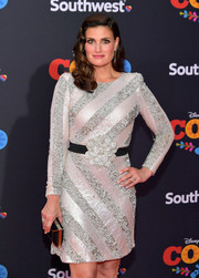 Idina Menzel paired a black and gold box clutch with a silver sequin dress for the premiere of 'Coco.'