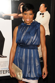 "Actress Regina King showed off her short cropped hairstyle while attending the ""Our Family Wedding"" premiere. She sported a chiffon ruffled dress with a cinched waist and gold clutch."