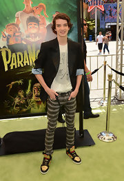Kodi Smit-McPhee, at the Los Angeles premiere of 'ParaNorman,' complemented his black-and-white outfit with a pair of gold, black, and red Converse CONS skateboarding sneakers.