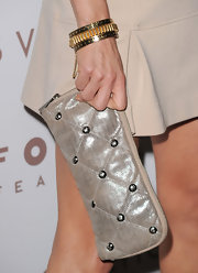 Juliette Lewis paired a nude colored dress with a metallic champagne-hued clutch. The quilted purse was embellished with silver studs.