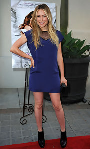 Sarah Carter paired her navy shift dress with a pair of black platform ankle boots.