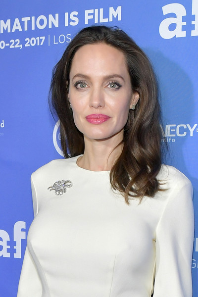 Angelina Jolie styled her simple white dress with a Beladora diamond brooch.