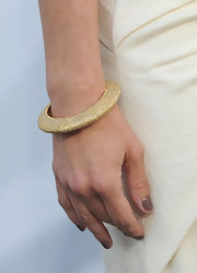 Charisma paired her cream halter dress with gold bangle bracelets.