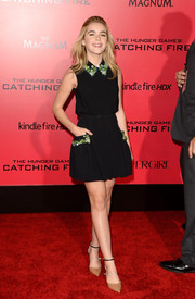 Kiernan Shipka completed her cute attire with a black Miu Miu mini skirt.