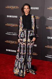 Meta Golding looked effortlessly chic at the 'Hunger Games: Mockingjay - Part 2' premiere in a floor-sweeping shirtdress by Mario Dice, featuring colorful embroidery on sheer black fabric.