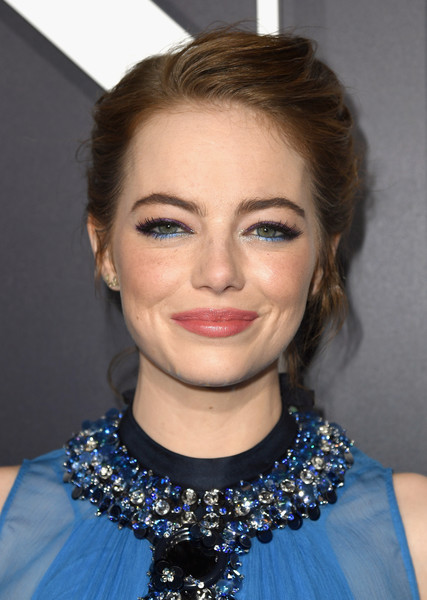For her beauty look, Emma Stone embraced color, teaming purple and blue eyeshadow with pink lipstick.