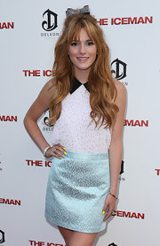 Bella Thorne's youthful ensemble at the 'Iceman' premiere consisted of a sleeveless white pin-dot blouse and a blue mini skirt.