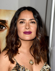 Salma Hayek adorned her decolletage with a multicolored gemstone pendant.