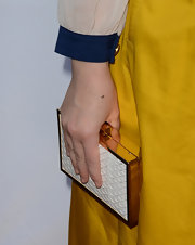 Amber topped off her red carpet look with this gold and white hard case clutch.
