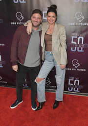 Kendall Jenner made an appearance at the premiere of 'The 5th Quarter' wearing torn Danielle Guizio boyfriend jeans and a sheer top.
