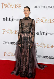 With its long sleeves and high neck, Angela Sarafyan's Reem Acra lace gown at the premiere of 'The Promise' looked deceptively modest, but that sheer fabric sure flaunted plenty of skin!