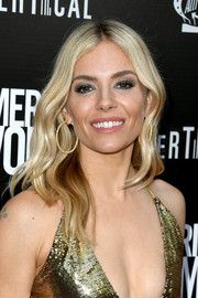 Sienna Miller accessorized with a pair of gold hoops to match her sequined dress.
