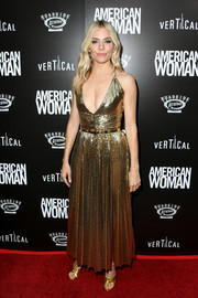 Sienna Miller lit up the red carpet with her gold sequined halter dress at the premiere of 'American Woman.'