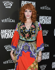 Christina Hendricks paired a textured gold box clutch with a colorful print dress for the premiere of 'American Woman.'