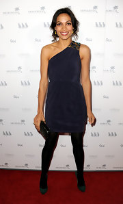 Rosario Dawson added shine to her look with a woven black hard case clutch.