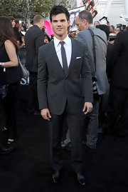 Taylor looked handsome in a tailored gray suit with a white shirt and a striped tie.