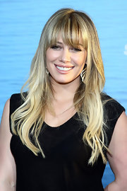 Hilary Duff attended the premiere of 'Soul Surfer' with styled curls and wispy bangs that peaked past her brows. Shimmering highlights completed her golden look.