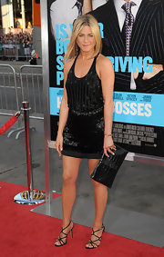 Jennifer Aniston teamed her shimmery LBD with strappy black satin sandals.