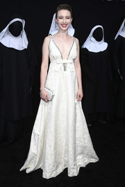 Taissa Farmiga complemented her dress with a white satin clutch.