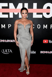 Demi Lovato matched her gown with a pair of gray ankle-strap sandals by Cesare Paciotti.