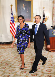 Michelle Obama attended the signing of the Caregivers/Veterans Health Services Act wearing black peep-toes with a print dress.