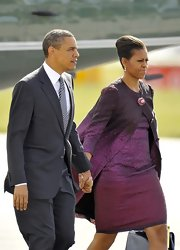 Michelle looked lovely leaving the UK in a purple ombre jacquard cocktail dress and matching coat.