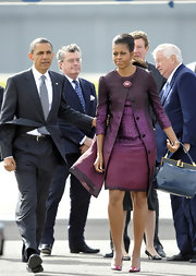 Michelle Obama left UK for the G8 Summit looking stylishly retro in this coat dress and framed navy leather tote combo.