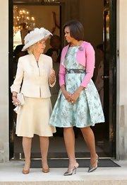 Michelle Obama styled her stylish aqua brocade dress with pointy pewter pumps.