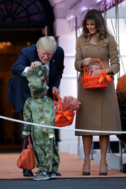 Melania Trump was classic in a double-breasted beige wool coat by Bottega Veneta while hosting Halloween at the White House.