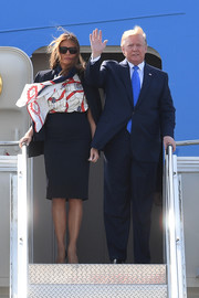 Melania Trump touched down in London wearing a navy skirt suit by Michael Kors.