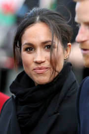 Meghan Markle stayed warm with a plain black scarf while visiting Cardiff Castle.