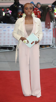 Laura Mvula chose a pale pink pantsuit with wide legs and a belted waist for her unique red carpet look.