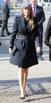 Princess Beatrice donned a stylish navy coat, which she cinched with a wide belt for a more curvy silhouette during the memorial service for David Frost.