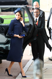 Meghan Markle kept it understated in a navy coat by Givenchy at Princess Eugenie's wedding.