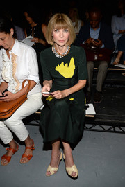Anna Wintour donned a forest green dress with bright yellow accents for the Proenza Schouler fashion show.