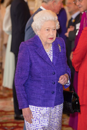 Queen Elizabeth II layered a purple blazer over a polka-dot dress, both by Stewart Parvin, for the 50th anniversary of the Prince of Wales' investiture.
