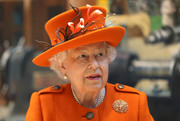 Queen Elizabeth II accessorized with a flower-accented orange hat to match her coat while visiting the Science Museum.