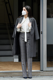 Queen Letizia of Spain teamed a white tie-neck blouse with plaid trousers and a wool coat for a meeting at the Spanish Association Against Cancer.