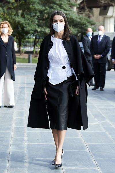 Queen Letizia of Spain teamed a black leather pencil skirt with a fitted white blouse and a cape coat for the Rare Diseases World Day event.