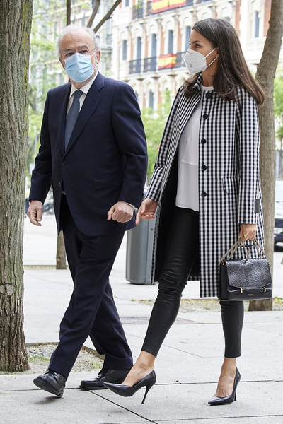 Queen Letizia teamed her coat with black leather pants and a white blouse.