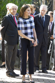 Queen Letizia of Spain was casual-chic in a gingham knit top and nautical trousers while visiting a traditional students' residence in Madrid.