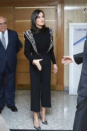 Queen Letizia of Spain visited the Foundation Against Drug Addiction headquarters wearing a black Uterqüe sweater with white swirl embroidery.