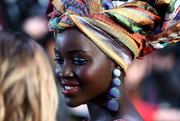Lupita Nyong'o teamed winged blue eyeshadow with statement earrings and a colorful head wrap for a totally vibrant look during the 'Queen of Katwe' London premiere.