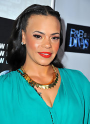 A bright and bold orange-red lipstick brought out the golden hues in Faith Evans' cheeks.