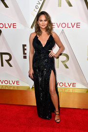 Chrissy Teigen went majorly sexy at the #REVOLVEawards in a black gown that boasted a plunging neckline, a curve-hugging silhouette, and a thigh-high slit!